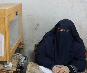 A representative for an Egyptian candidate watches a ballot box during a second round election held in December 2011