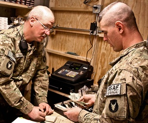 Two soldiers count sales at a new post exchange at Forward Operating Base Mehtar