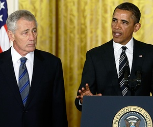 President Obama standing with Defense Secretary Chuck Hagel and CIA Director John Brennan. Hagel served as an infantryman in the Vietnam War