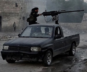 Syrian rebels firing heavy machine gun at troops loyal to Syria's current president Bashar Assad