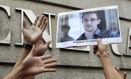 Someone holding a photograph of Edward Snowden, the NSA leaker at a protest