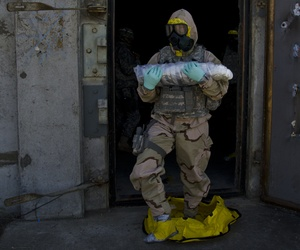 A member of the Army's explosive ordinance disposal team carries a decontaminated chemical round from a storage facility during a training exercise
