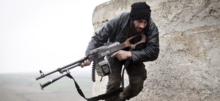 A Syrian opposition fighter running from opposing fire