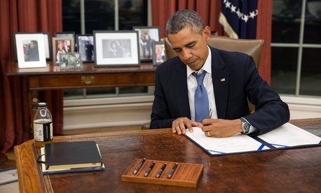 President Barack Obama signs H.R. 3210, the Pay Our Military Act, which Congress passed just hours before shutting down the federal government, Sept. 30, 2013.