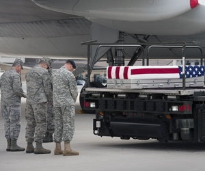 Troops say a prayer beside the transfer case containing the remains of Army Sgt. Michael Cable, 26, of Philpot, Ky., at Dover AFB in March.