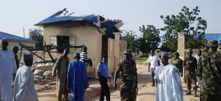 Nigerian government officials stand next to a house damaged by a Boko Haram attack