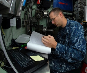 A corpsman examining medical records aboard the USS Montpelier