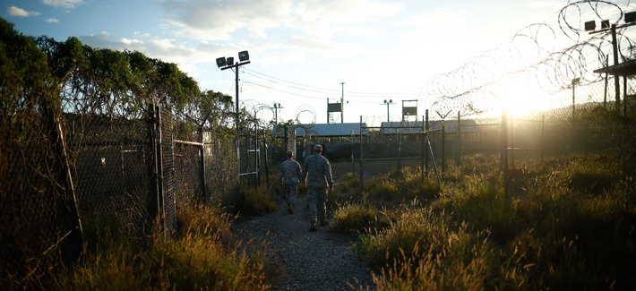 A soldier walks through Camp X-Ray, one of the abandoned facilities at Guantanamo Bay