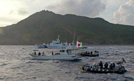 Japanese Coast Guard vessels sail alongside protestors near one of the Diaoyu/Senkaku Islands