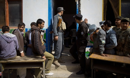 Afghan men wait in line to get their registration card on the last day of voter registration for the upcoming presidential elections outside a school in Kabul, Afghanistan, Tuesday, April 1, 2014.