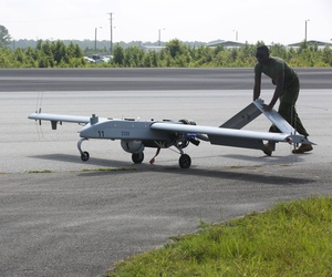 An avionics maintenance technician pushes an RQ7-B drone back to the taxiway after landing