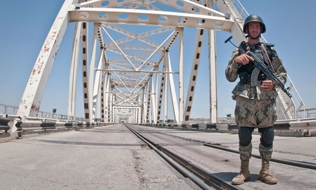 An Afghan Border Policeman guards the Freedom Bridge crossing the Amu Darya River in northern Afghanistan's Balkh Province, May 2010.