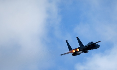A U.S. F15C Eagle jet fighter flies over Lithuania for a NATO exercise at the Siauliai airbase, April 2, 2014.