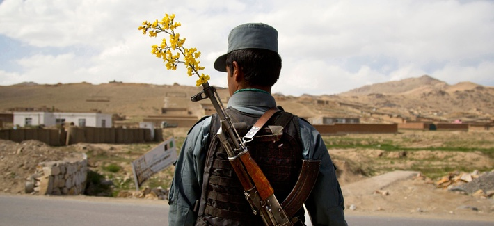 An Afghan National Police Officer stands by a checkpoint on the outskirts of Maidan Shahr, Wardak province, Afghanistan