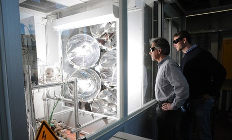 Two men looking at the Solar Jet reactor at work