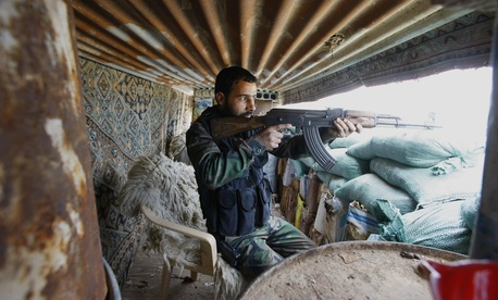 A Shiite fighter with the Hussein Brigade fires his weapon during a skirmish with the Free Syrian Army in Hatita, Syria on November 22, 2013.