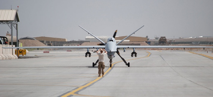An airman with the 451st Air Expeditionary Group motions towards a MQ-9 Reaper drone taxiing at Kandahar Airfield, Afghanistan on March 20, 2014.