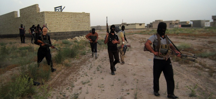 Masked anti-government gunmen patrol the streets in Fallujah, Iraq on April 28, 2014.