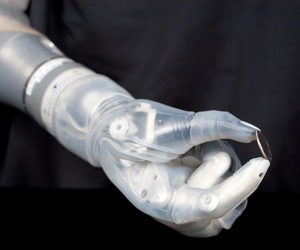 The DEKA Arm System, a product of DARPA's Revolutionizing Prosthetics program, is seen here holding a coin.