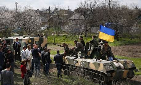 A group of people block a column of Ukrainian Army vehicles en route to Kramatorsk, Ukraine on April 16, 2014.