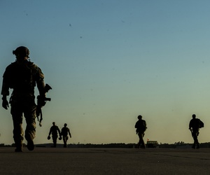 Soldiers with the 20th Special Forces Group walk a flight line during 2014 Emerald Warrior exercises