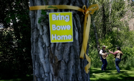 "A yellow ribbon and a sign honoring captive U.S. Army Sgt. Bowe Bergdahl are seen on a tree as J.C. Needham and wife Sonja, right, rehearse to perform at the ""Bring Bowe Back"" celebration in Hailey, Idaho, June 22, 2013."