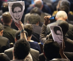 Participants at NETmundial, a major conference on the future of the internet, hold up pictures of NSA leaker Edward Snowden on April 23, 2014.