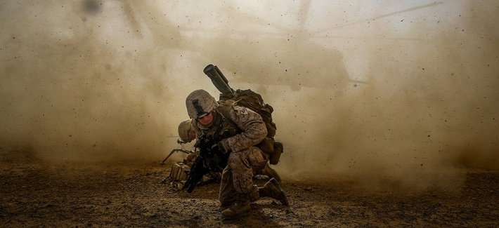 A Marine Corps corporal shields himself from dust kicked up by a CH-53E Super Sea Stallion lifting off during a mission in Helmand Province, Afghanistan, on April 28, 2014.