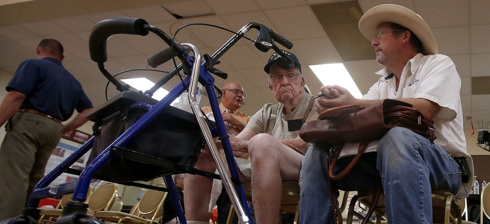 A World War 2 veteran and his son wait to speak to someone at a health care crisis center set up by the American Legion, on June 10, 2014.