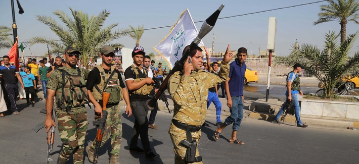 Shiite tribal fighters raise their weapons and chant slogans against the ISIS in Baghdad's Shula neighborhood, on June 16, 2014.