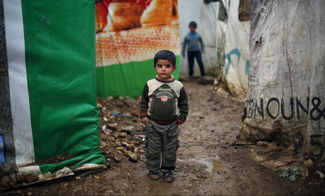A Syrian boy stands and watches in the Fedaya Camp, 25 miles east of Beirut, on June 19, 2014.