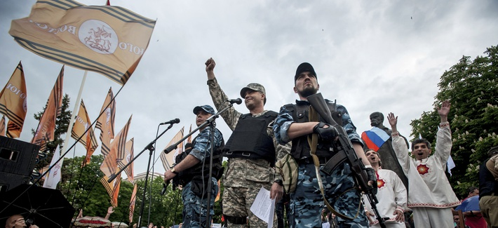 Pro-Russian gunmen react whie listening to a speaker as they declare independence for the Luhansk region in eastern Ukraine, on May 12, 2014.