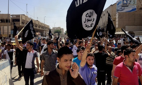 Pro-ISIL demonstrators chant and wave flags in front of the provincial government headquarters building in Mosul, on June 16, 2014.
