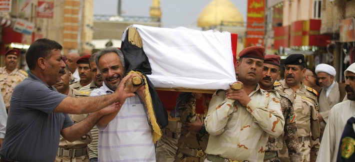 Mourners carry the flag draped coffin of an Iraqi Army colonel who was killed by Al Qaeda fighters, on April 14, 2014.