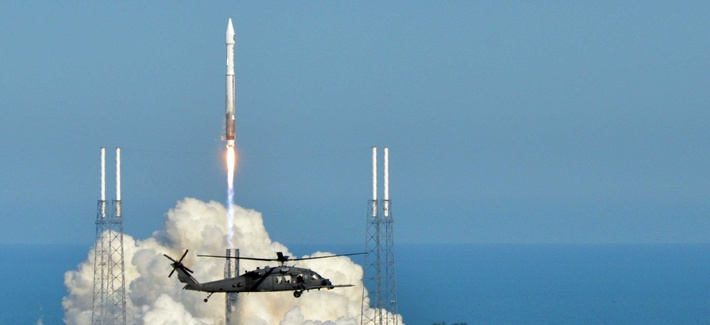 An Air Force helicopter flies by as an Atlas V rocket carrying a Space Based Infrared System GEO-2 rocket launches from Cape Canaveral, on March 21, 2013