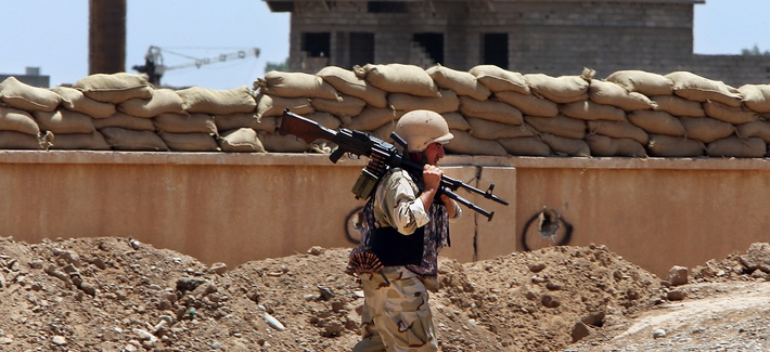 A Kurdish peshmerga fighter carries his weapon to a base near the oil-rich province of Kirkuk in Northern Iraq, on June 25, 2014.