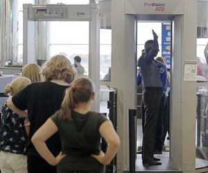 Passengers are scanned by TSA officers at a security checkpoint at Logan Airport in Boston, on October 24, 2012.