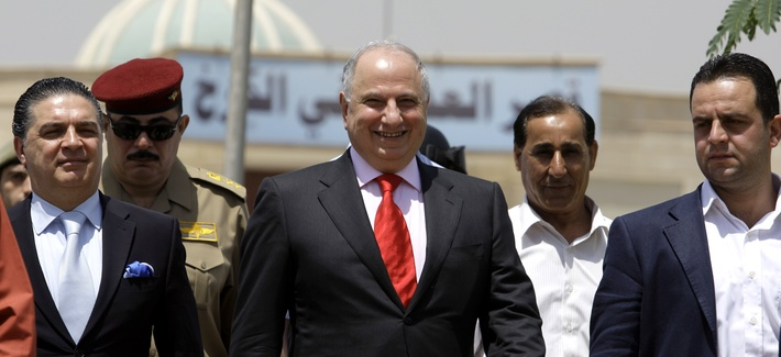 Ahmed Chalabi exits a courthouse flanked by security guards in Baghdad, Iraq, on May 12, 2009.