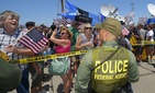 Immigration demonstrators in Murietta, Calif., yell to a Customs and Border Protection officer, on July 4, 2014.