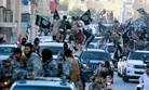ISIL militants in Raqqa, Syria, wave flags during a military parade, on June 30, 2014.