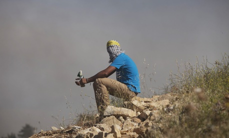 A masked Palestinian youth holds a Molotov cocktail during clashes with Israeli soldiers outside Ofer near the West Bank city of Ramallah on May 16, 2014.
