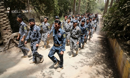 Iraqi police officers and new recruits march at a recruiting office in Baghdad, Iraq, on July 5, 2014.