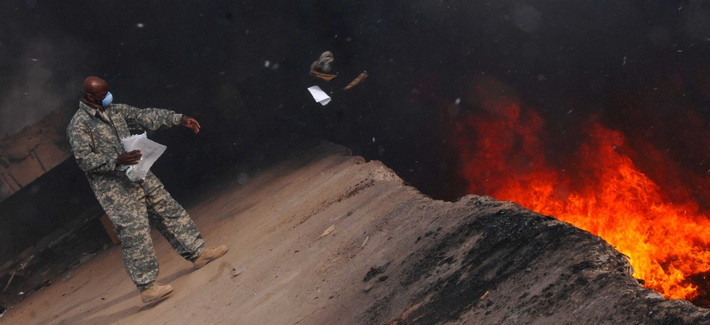 A sergeant tosses unusable uniform items into a burn pit at a base in Balad, Iraq, on March 10, 2008.