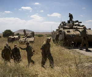 Israeli soldiers work on their tanks close to the Quneitra border crossing in the Golan Heights, on June 22, 2014.
