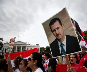 Protesters carry an image of Syrian President Bashar Hafez al-Assad during a demonstration against US military action in Syria, Sept. 9, 2013, in front of the White House in Washington.