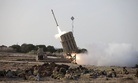 Israeli soldiers take cover as an Iron Dome battery fires a rocket near the city of Ashrod, on November 19, 2012.