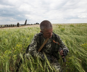 A pro-Russian fighter collects ammunition from the site of remnants of a downed Ukrainian army aircraft Il-76 at the airport near Luhansk, Ukraine, June 14, 2014.