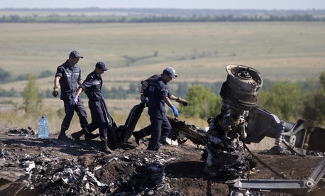 Ukrainian emergency workers on Monday carry a victim's body in a plastic bag at the crash site of Malaysia Airlines Flight 17.