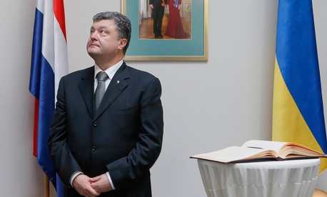 Ukrainian President Petro Poroshenko visits the Dutch embassy in Kiev on July 21, 2014, to lay flowers and sign a condolence book in memory of the people who died during the Malaysia Airlines flight MH17 crash in eastern Ukraine.