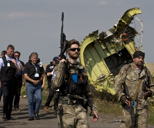 Pro-Russian fighters walk past the wreckage of Malaysia Airlines Flight 17 near the village of Hrabove, in eastern Ukraine.